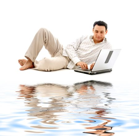 relaxed man with laptop computer on white sand