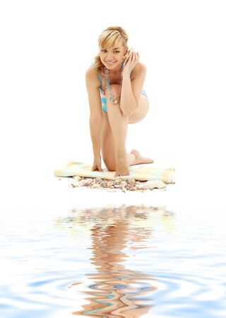 lovely blond in blue bikini with shell on white sand photo