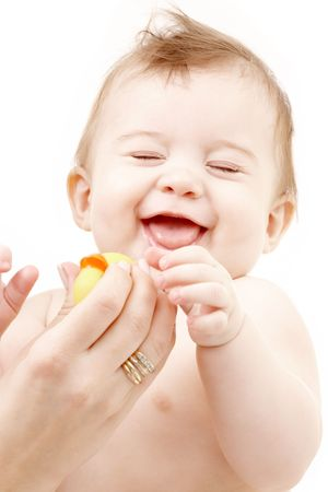 laughing baby: portrait of laughing baby boy in mother hands playing with rubber duck