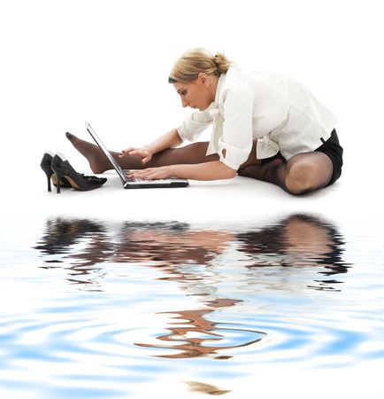 flexible businesswoman with laptop computer on white sand photo