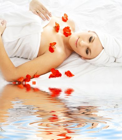 remedial: beautiful lady with red flower in spa with water