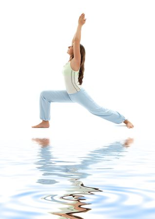 virabhadrasana: sporty girl practicing virabhadrasana warrior pose on white sand