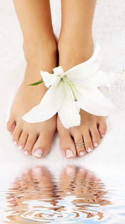 aqua naked: beautiful lady feet with madonna lily in spa