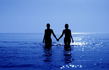 silhouette image of two bikini girls holding hands