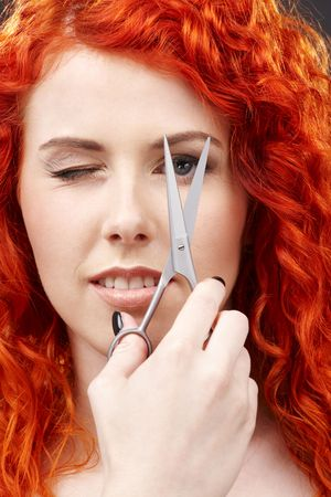cutting through: picture of lovely redhead with scissors over grey LANG_EVOIMAGES