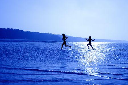 silueta de imagen de dos niñas corriendo en el agua