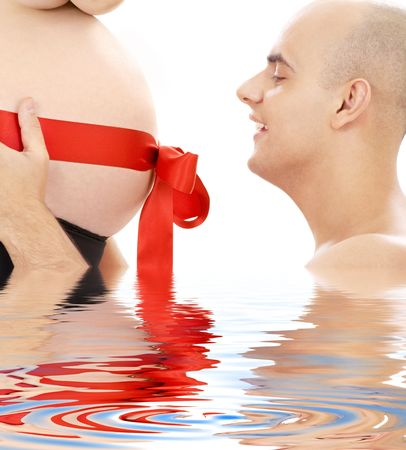 happy man holding belly of pregnant woman in water Stock Photo - 3084028