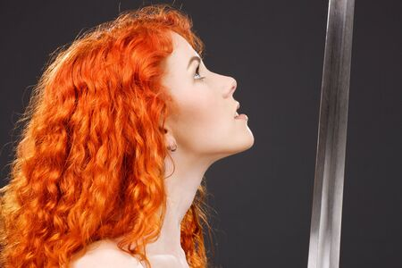 lovely redhead with medieval sword over grey Stock Photo - 3199772