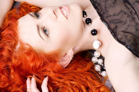 carnal: picture of curly redhead woman over grey