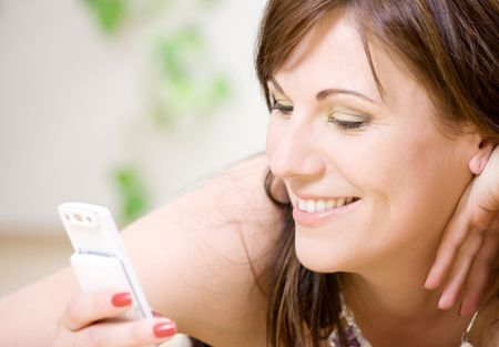 portrait of happy woman with white phone (focus on smile) Stock Photo - 3199833