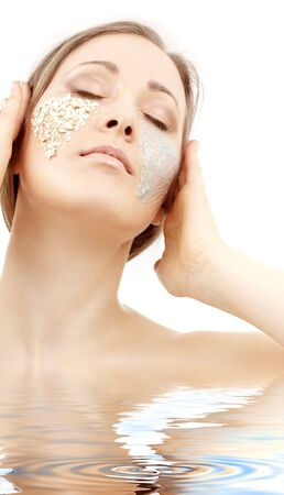 exfoliation: beautiful woman with gel and scrub on face in water LANG_EVOIMAGES
