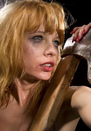 beaten woman: dark bizarre portrait of wild redhead girl with axe