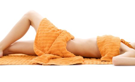 rejuvenating: torso of relaxed lady with orange towels over white