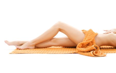 depilation: long legs of relaxed lady with orange towel over white LANG_EVOIMAGES