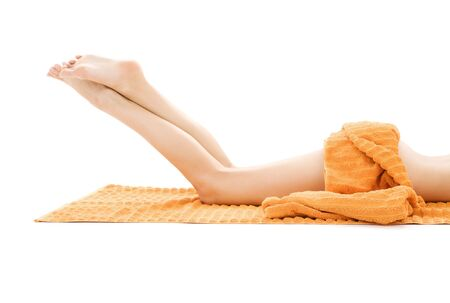 long legs of relaxed lady with orange towel over white Stock Photo - 3307831