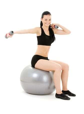 balance ball: lovely fitness instructor with dumbbells on pilates ball