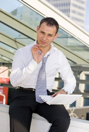 ensuring: picture of handsome businessman with white laptop computer