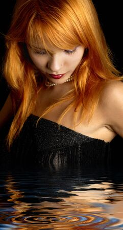 dark portrait of lovely redhead in water