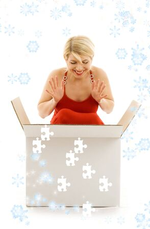 happy girl with puzzle box surrounded by snowflakes photo
