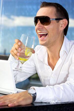 picture of handsome man with glass of water and laptop Stock Photo - 3465183
