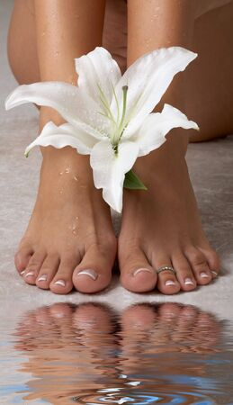 aqua naked: beautiful female feet with madonna lily in spa