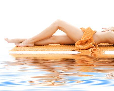 cellulite: largo de piernas relajado dama naranja con una toalla sobre la arena blanca  LANG_EVOIMAGES