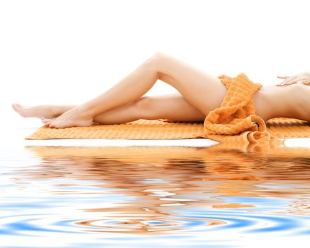 cellulite: long legs of relaxed lady with orange towel on white sand LANG_EVOIMAGES