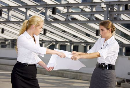 picture of two angry businesswomen fighting for contract Stock Photo
