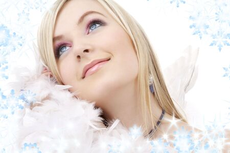 feather boa: portrait of happy blond angel girl with feather boa and snowflakes LANG_EVOIMAGES
