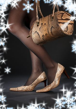 bodyscape: long legs in snakeskin shoes with handbag and snowflakes