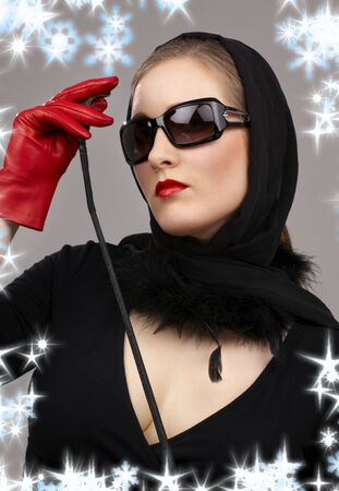 female domination: portrait of lady in black headscarf and red gloves with crop