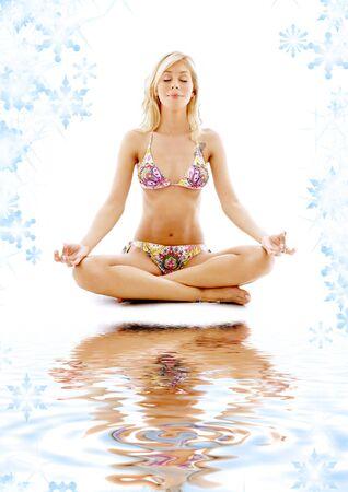 vivifying: meditating blonde in bikini on white sand