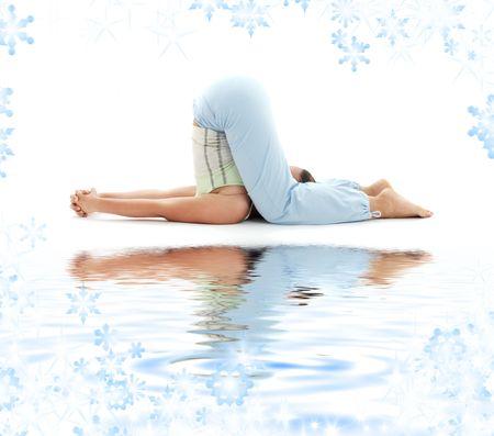 sporty girl practicing halasana plow pose on white sand Stock Photo - 3660674