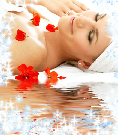 rejuvenating: beautiful lady with red flowers in spa