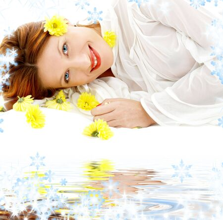 portrait of lovely beauty with yellow flowers on white sand photo