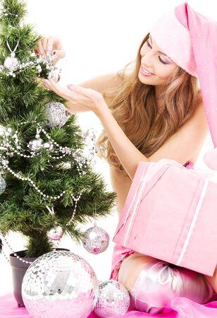 lovely santa helper girl with gift box decorating christmas tree Stock Photo