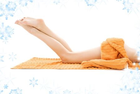 long legs of relaxed lady with orange towel and snowflakes Stock Photo - 3804266