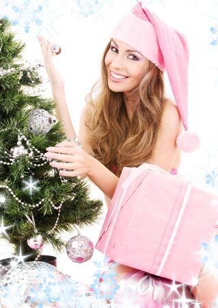 decorating christmas tree: lovely santa helper girl with gift box decorating christmas tree LANG_EVOIMAGES