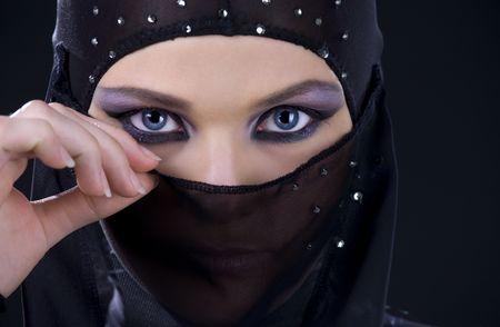 hidden danger: closeup picture of ninja face in the dark