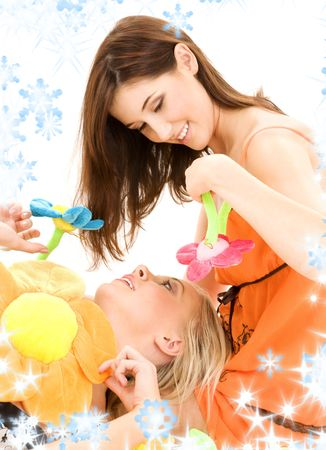 careless: two happy teenage girls playing with plush flowers