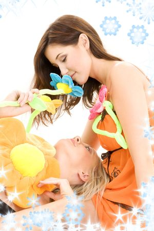 two happy teenage girls playing with plush flowers photo