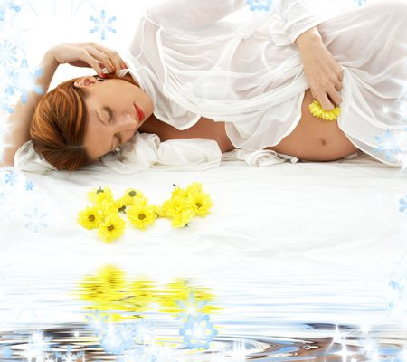 beautiful pregnant redhead woman with yellow flowers photo