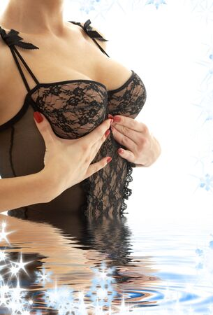 lady in black lingerie pushing breasts up Stock Photo