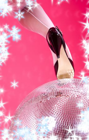 leg in high heels shoe and disco ball over pink (focus on ball) Stock Photo