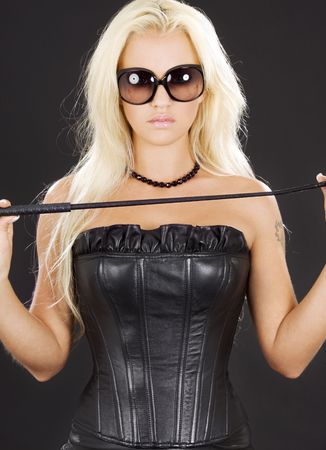 dominatrix in black leather corset with riding crop Stock Photo - 4097536
