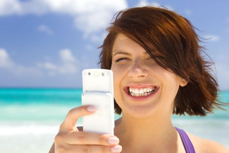 happy woman with white phone on the beach Stock Photo - 4211828