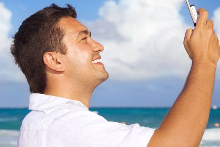 happy man with cell phone on the beach