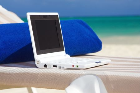 web access: laptop computer and towel on the beach chaise longue