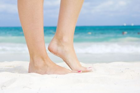 woman foot: tanned legs of woman standing on the beach