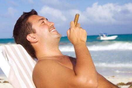 cigar smoking man: imagen de hombre relajado con cigarros en la playa